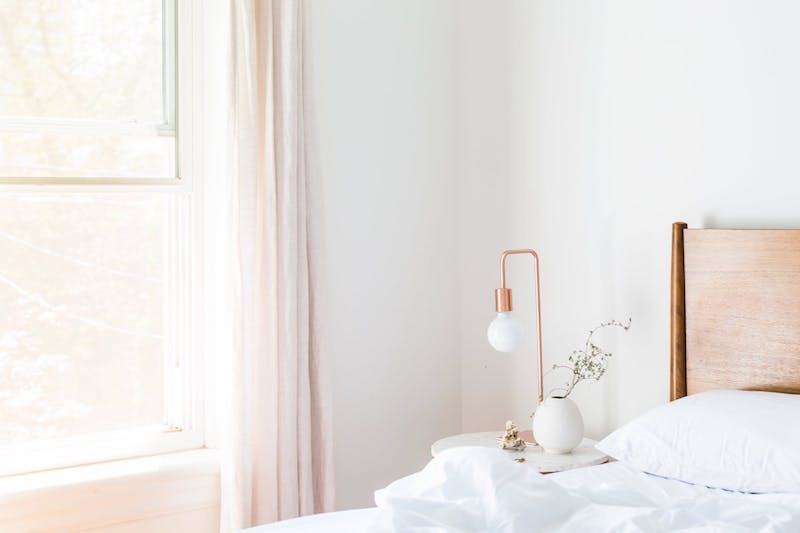 приліжкова лампа у світлій спальні